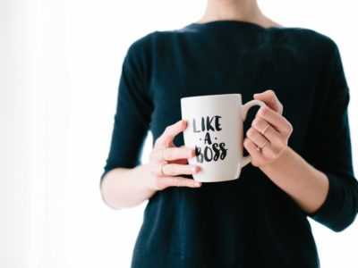Woman in black holding mug with the words 'like a boss' on it, while working on business solutions for small business