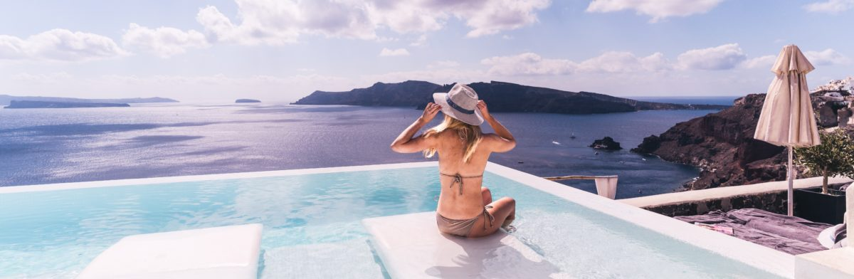 woman sits by a pool looking at an amazing view, after discovering how to go on holiday when running a small business