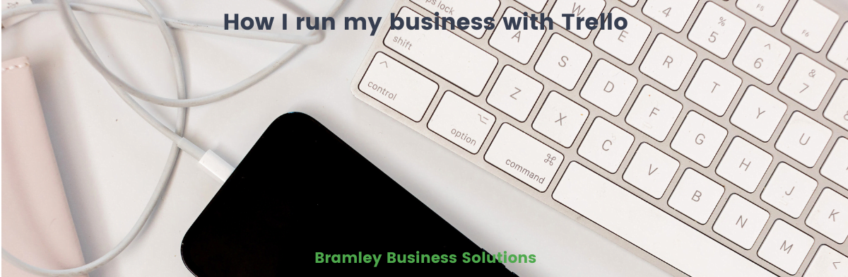 keyboard, cable and phone on a desk with title of blog overlaid How I run my business with Trello